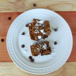 dark chocolate chip cookie bars on a plate with powdered sugar